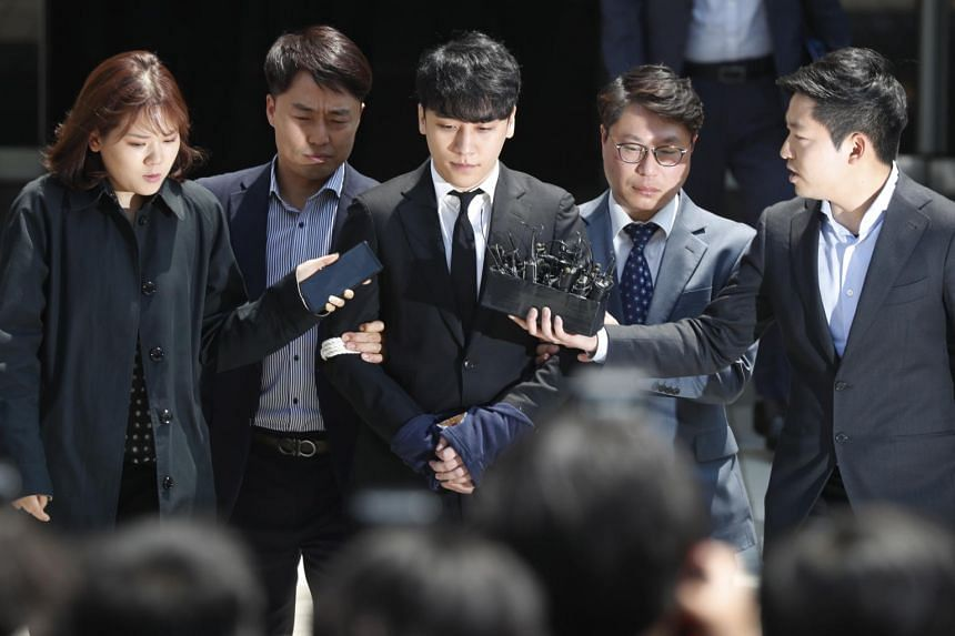 Former BigBang singer Seungri (centre) is said to have booked prostitutes for would-be investors of his businesses and siphoned 530 million won (S$612,000) from nightclub Burning Sun.
