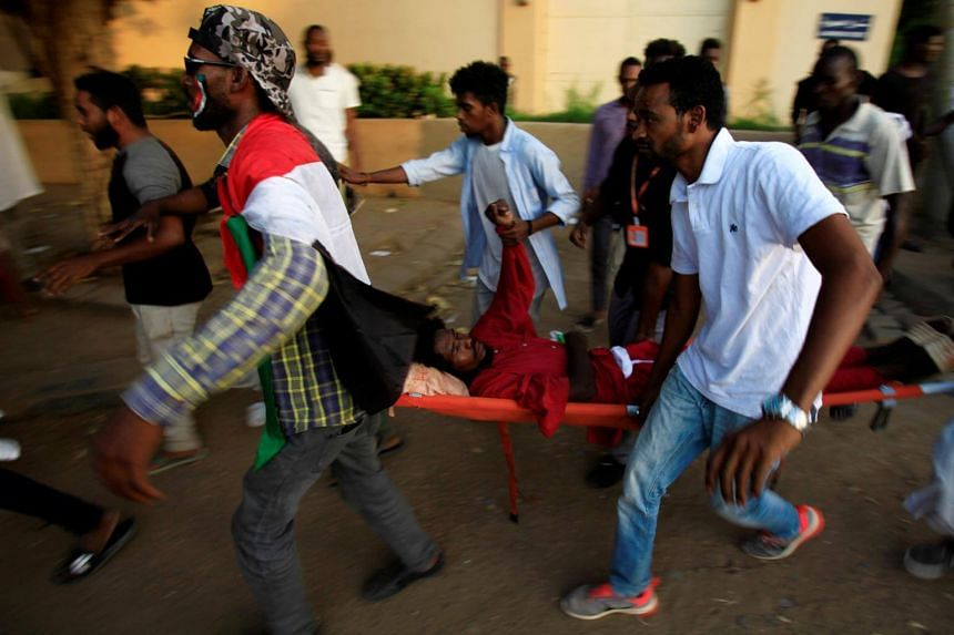 Civilians evacuate a Sudanese protester injured during demonstrations along a street in central Khartoum, Sudan, on May 15, 2019.