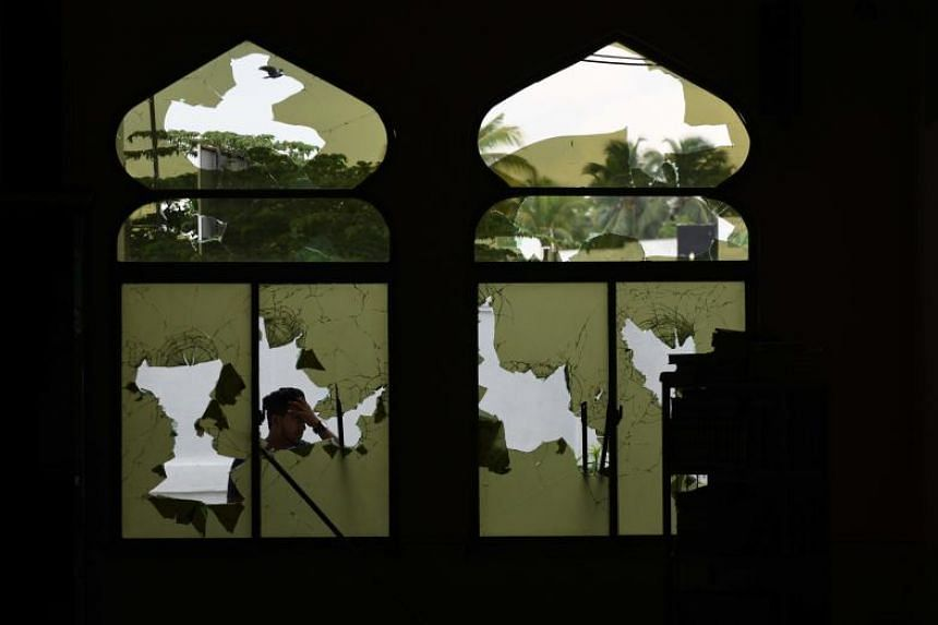 A Muslim man peers through shattered windows at the Jumha mosque after a mob attack in Minuwangoda on May 14, 2019.