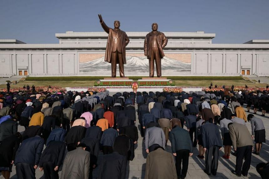 People bow as they pay their respects before the statues of late North Korean leaders Kim Il Sung and Kim Jong Il on Mansu hill in Pyongyang, on April 15, 2019.