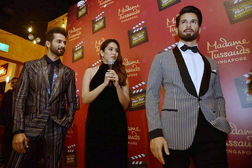 Bollywood actor Shahid Kapoor (left) and his wife Mira Rajput standing together with his wax statue at Madame Tussauds Singapore in Sentosa, on May 16, 2019.
