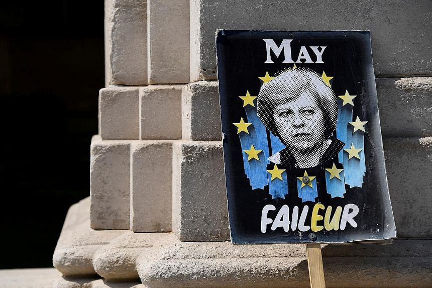 An anti-Brexit placard depicting British Prime Minister Theresa May near the Houses of Parliament in London yesterday. PHOTO: REUTERS