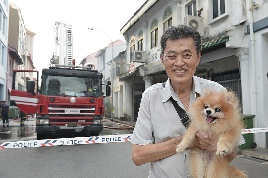 Mr Peter Lim with his dog Lucky, which he had left in his house when he rushed out in a panic but which was later rescued by the police. Mr Lim Hock Seng, owner of the shophouse in Dickson Road where a fire broke out (right), said none of the occupan