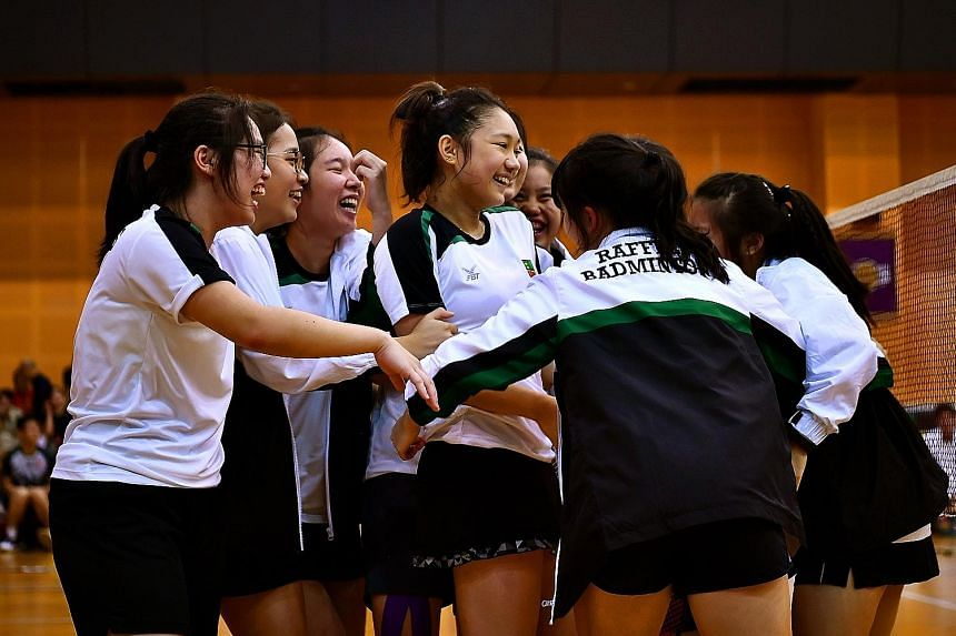 The RI A Division badminton girls celebrating after securing their winning point in the second doubles against HCI yesterday. ST PHOTO: LIM YAOHUI