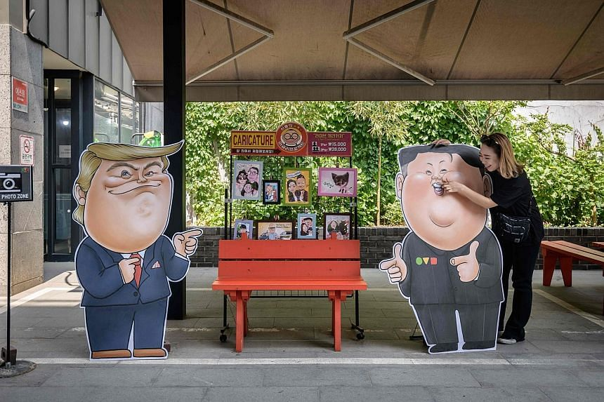 Caricatures of US President Donald Trump (left) and North Korean leader Kim Jong Un outside a shop in Seoul yesterday. Mr Trump and South Korea's Mr Moon Jae-in will discuss efforts to denuclearise the North.