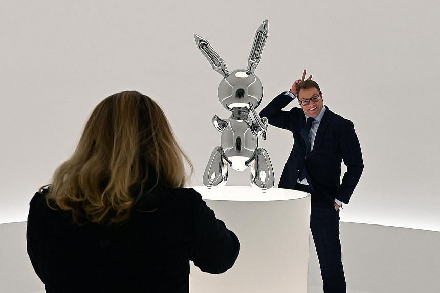A visitor (above) striking a pose next to artist Jeff Koons' (left) Rabbit sculpture at a preview for Masterpieces from The Collection of S.I. Newhouse at Christie's New York earlier this month.