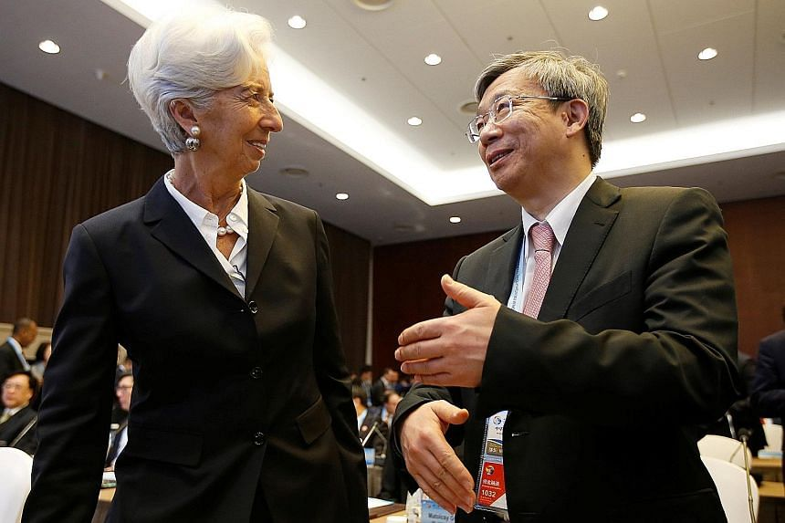 People's Bank of China governor Yi Gang chatting with International Monetary Fund managing director Christine Lagarde in Beijing last month. He has spent the past year saying that he wants to avoid a flood of stimulus, pushing back against expectatio