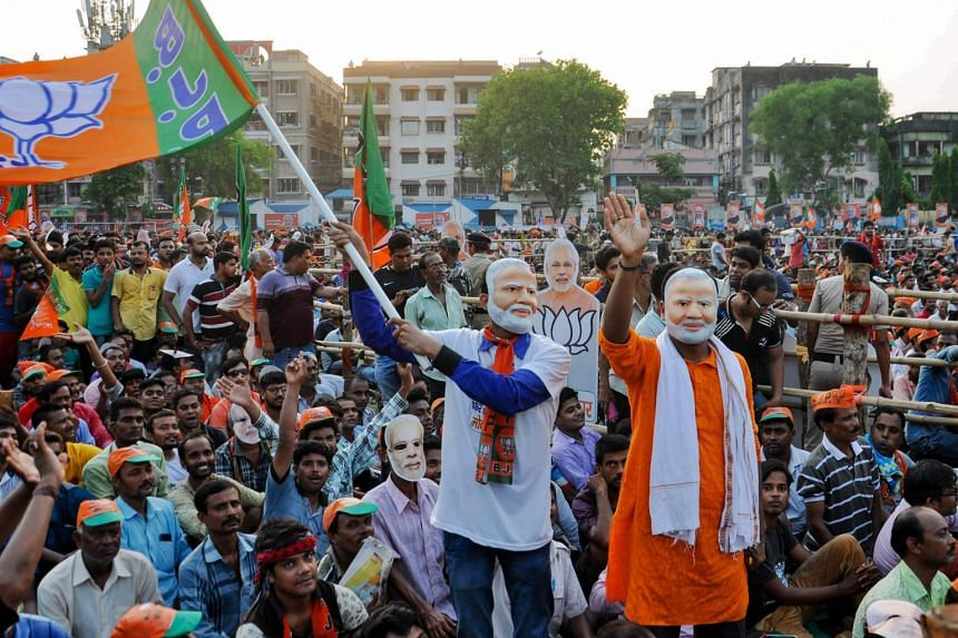 Supporters of the Bharatiya Janata Party wave a party flag as they wear masks of Prime Minister Narendra Modi during an election campaign led by Modi in Kolkata on May 16, 2019.