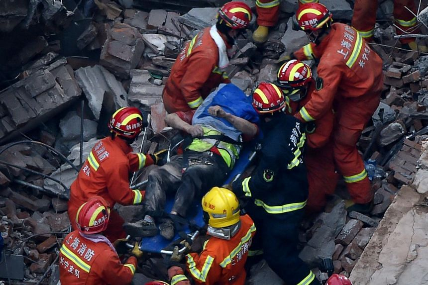 Members of a rescue team carry out a survivor of a building collapse in Shanghai on May 16, 2019.