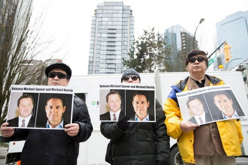 Protesters hold photos of Canadians Michael Spavor and Michael Kovrig outside British Columbia Supreme Court, in Vancouver on March 6, 2019.