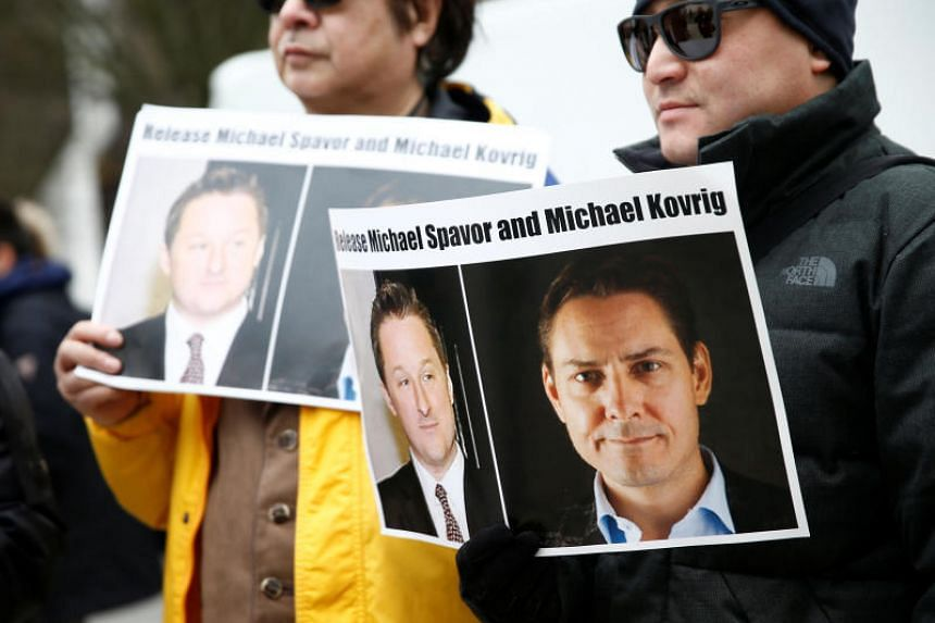 People hold signs calling for China to release Canadian detainees Michael Spavor and Michael Kovrig at the BC Supreme Court in Vancouver, British Columbia, Canada, on March 6, 2019.