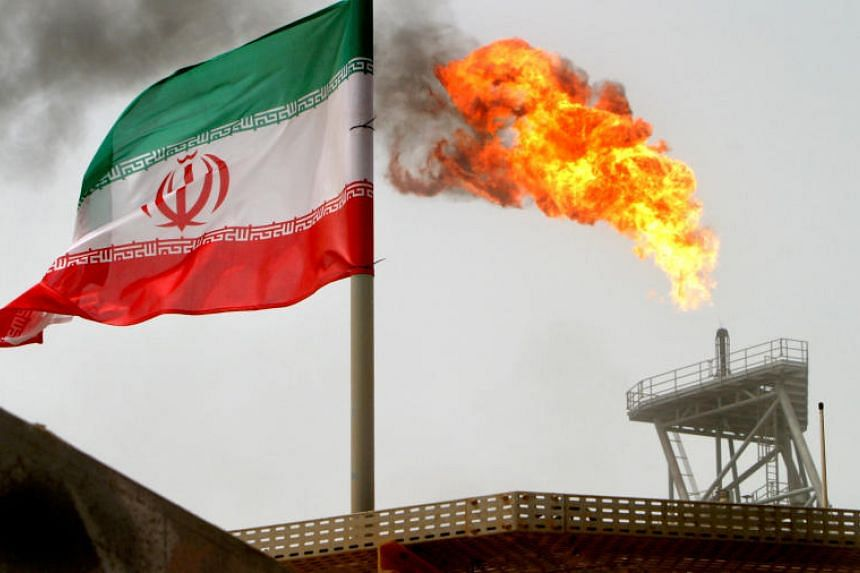 A gas flare on an oil production platform in the Soroush oil fields is seen alongside an Iranian flag in the Persian Gulf, Iran, on July 25, 2005.