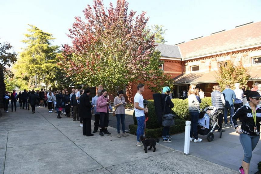 People wait in line to vote in the Australian fedral election outside the Malvern Early Voting Centre in Melbourne on May 17, 2019.
