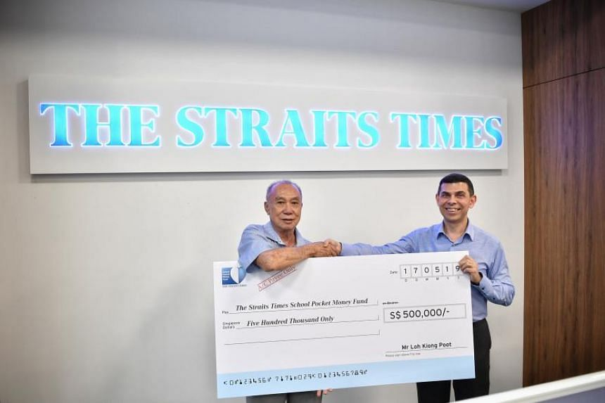 Retired businessman Mr Loh Kiong Poot (left) giving the mock cheque to Mr Warren Fernandez,  chairman of The Straits Times School Pocket Money Fund at The Straits Times newsroom on May 17, 2019.