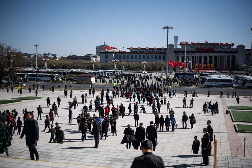"Officials and pedestrians outside the Great Hall of the People in Beijing, on March 12, 2019. The Communist Party's People's Daily described China's determination to protect its national interests and dignity as being as ""firm as a boulder""."