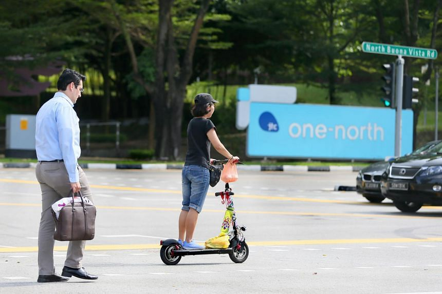 A woman on an e-scooter crossing the road in Bouna Vista.