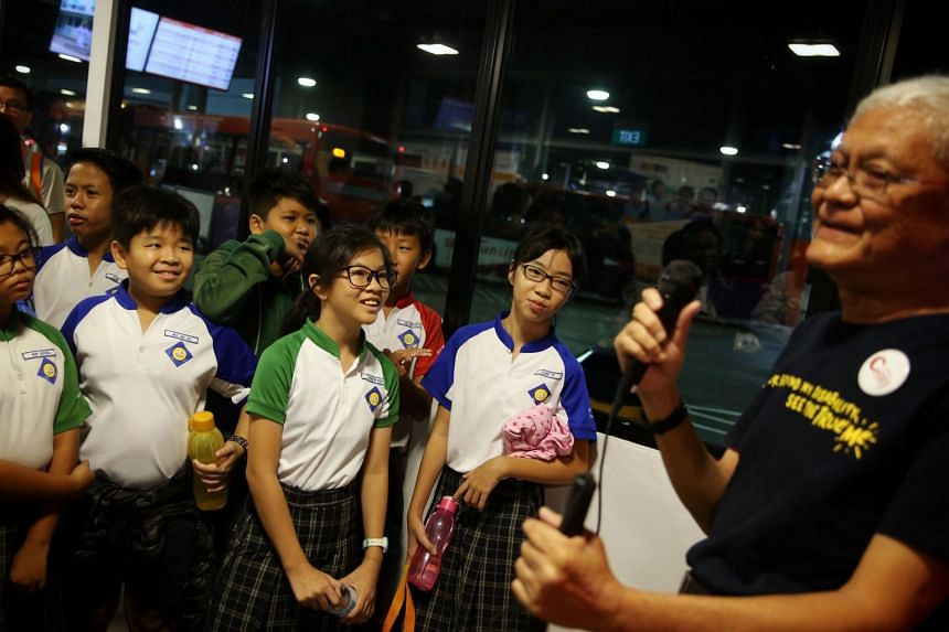 Sengkang Primary School students listen as Mr Lawrence Tan (left), who lost his sight to glaucoma, speaks about his experiences using public transport, at Sengkang Bus Interchange, on May 17, 2019.