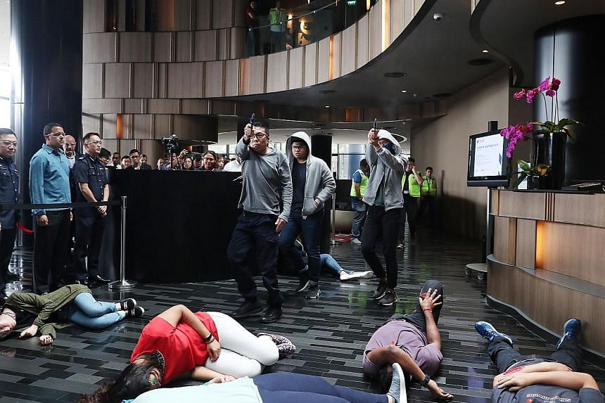 """Three """"gunmen"""" shooting down staff and tourists at Crowne Plaza Changi Airport yesterday, as part of a counter-terrorism exercise."""