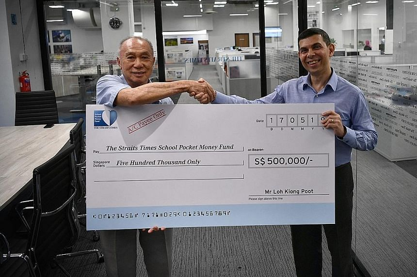 Retired businessman Loh Kiong Poot presenting a cheque for $500,000 to Mr Warren Fernandez, chairman of The Straits Times School Pocket Money Fund, at The Straits Times newsroom yesterday. Mr Loh, who also gave $500,000 to the fund last year, said he