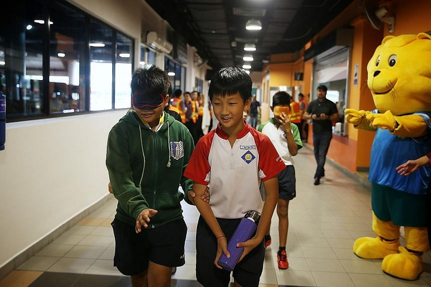 Above: Mr Lawrence Tan, 66, who is partially blind, spoke about his personal experiences on public transport at yesterday's exhibition launch. Left: Sengkang Primary School pupil Hedrian Al-Shahiryn Hairul Nizam, 12, wears a blindfold to simulate the