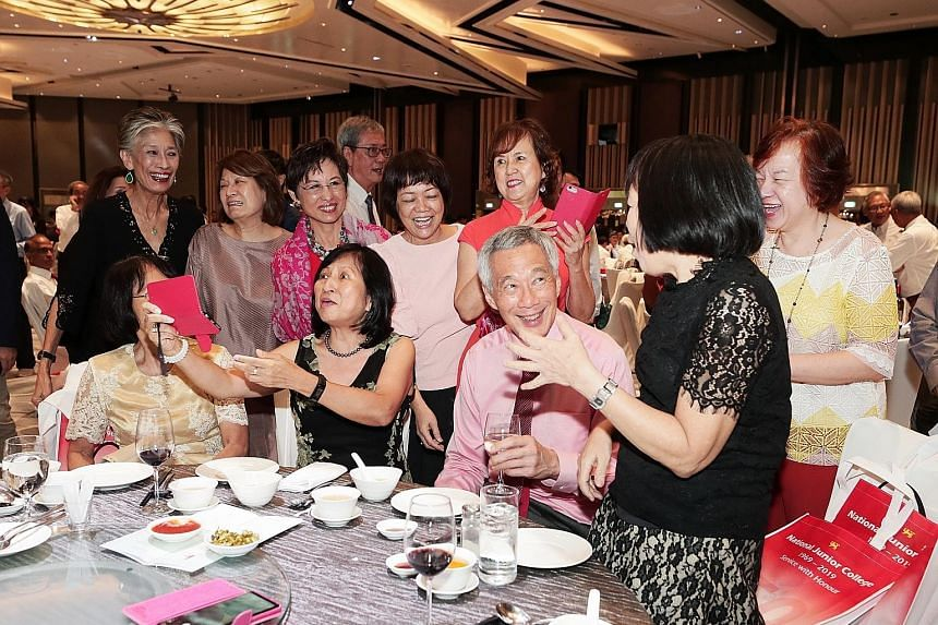Prime Minister Lee Hsien Loong interacting with fellow 1969 pioneer batch students of the National Junior College. He was guest of honour at a gala dinner yesterday to mark the school's 50th anniversary.