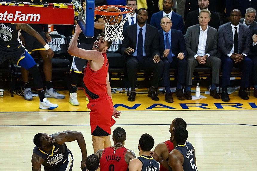 Golden State's Draymond Green (left) making a late basket for two of his 16 points against Portland Trail Blazers in Game 2 of the Western Conference Finals on Thursday. The Warriors won 114-111 to take a 2-0 lead. PHOTO: REUTERS