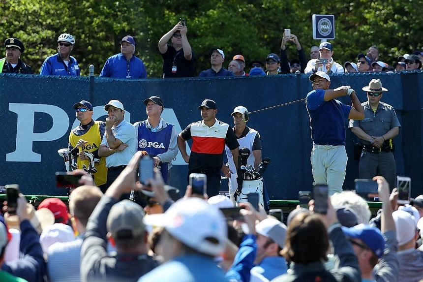 From right: Tiger Woods driving off from the 15th tee at the Bethpage Black course, watched by Brooks Koepka and Francesco Molinari during the first round of the 2019 PGA Championship on Thursday. PHOTO: AGENCE FRANCE-PRESSE