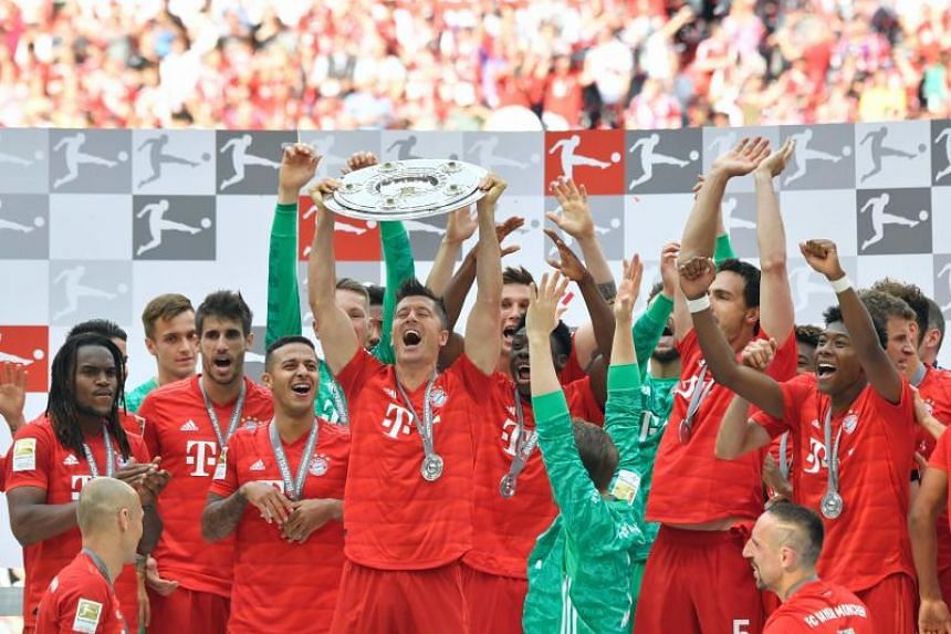 Bayern Munich players including Bayern Munich's Polish forward Robert Lewandowski celebrate with the trophy after the German First division Bundesliga football match FC Bayern Munich v Eintracht Frankfurt in Munich, southern Germany, on May 18, 2019.