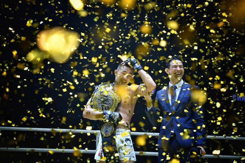 A jubilant Christian Lee at the Singapore Indoor Stadium last night after taking over the vanquished Shinya Aoki's One Championship lightweight belt.