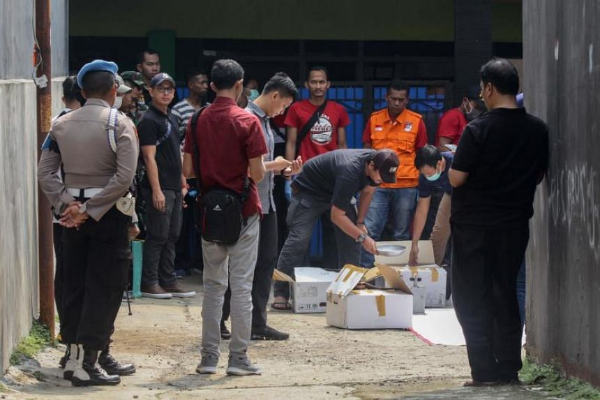 Anti-terror police officers collect evidence from a house at Nanggewer Mekar village in Cibinong, in Indonesia's West Java province, on May 18, 2019.