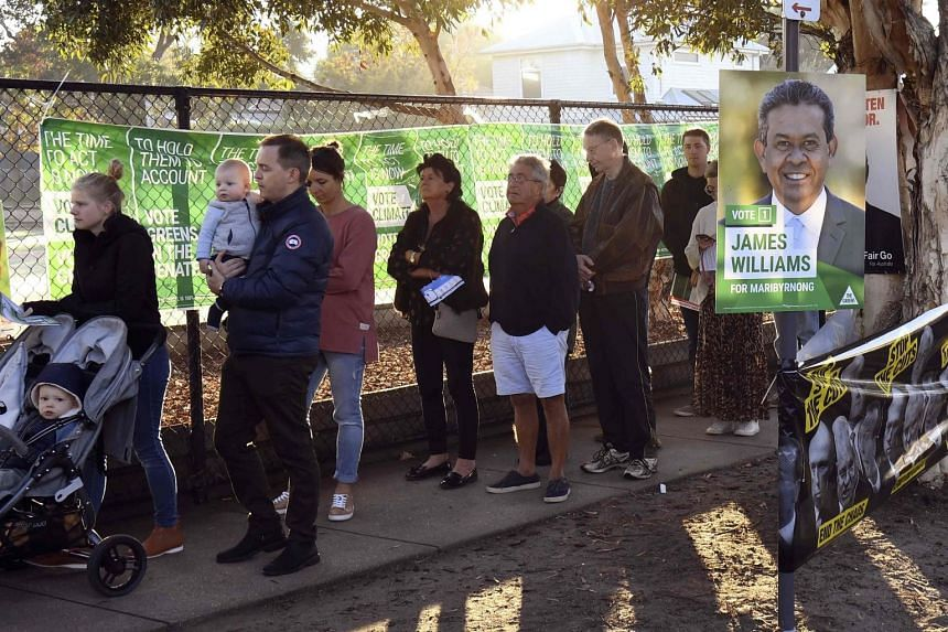 People queue in the early morning light in Melbourne to vote as polling booths open in Australia's general election on May 18, 2019.