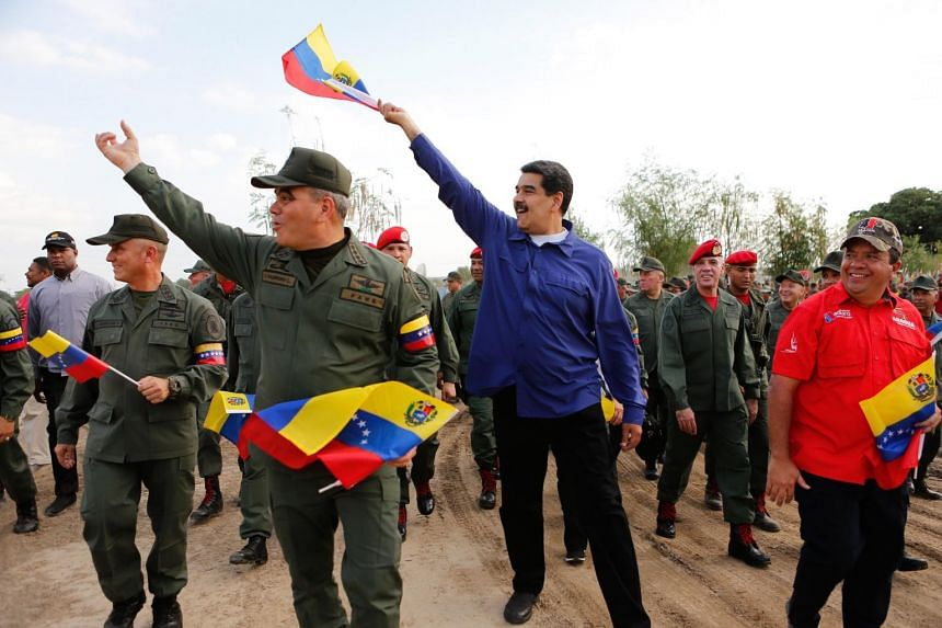 """President Nicolas Maduro (in blue) said on May 17 that talks with his country's opposition """"have begun nicely to move towards agreements of peace, agreement and harmony""""."""