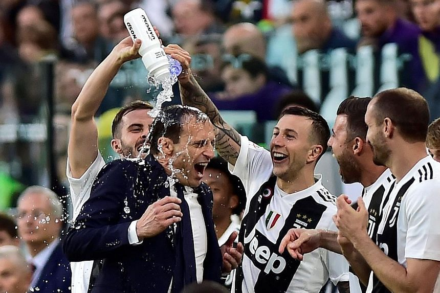 Coach Massimiliano Allegri celebrating Juventus' Serie A win with his players after beating Fiorentina 2-1 at home on April 20.
