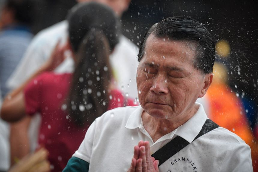 A man is blessed with holy water during Vesak Day celebrations at Thekchen Choling temple, on May 19, 2019.