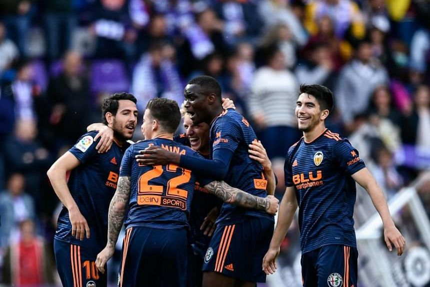 Valencia's players celebrate after winning the Spanish League football match between Real Valladolid and Valencia at the Jose Zorrilla stadium in Valladolid on May 18, 2019.