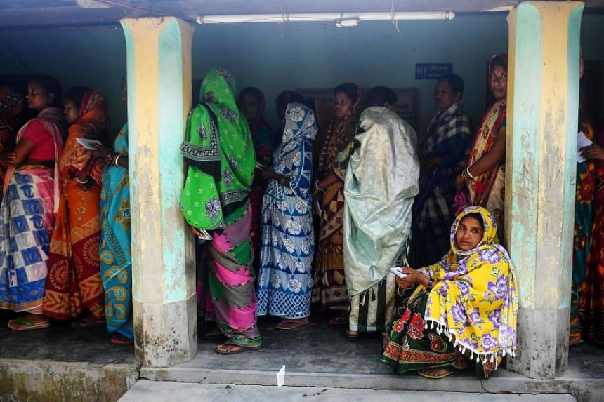 Indian voters queue to cast their votes in the Ghoramara island, which is sinking into the Bay of Bengal as a result of climate change.