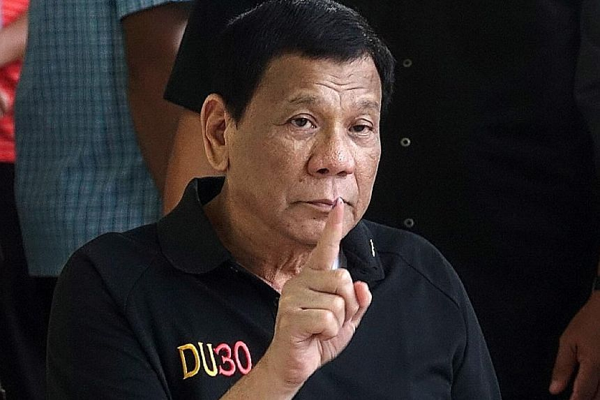 Philippine President Rodrigo Duterte showing the ink on his finger after casting his vote during the mid-term elections last week. His spokesman denied a media report that Mr Duterte had been in hospital since Friday. PHOTO: EPA-EFE