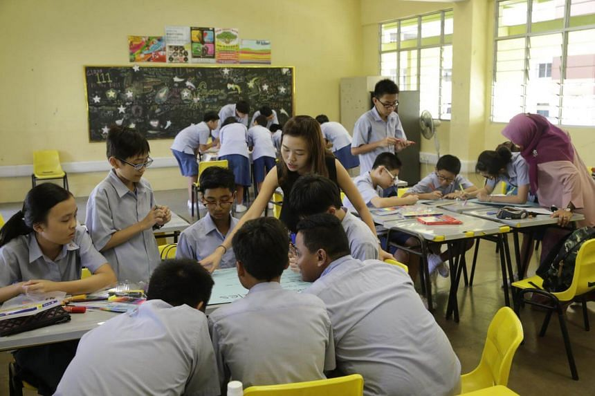 A teacher guiding her class during an activity to create a class motto and banners.
