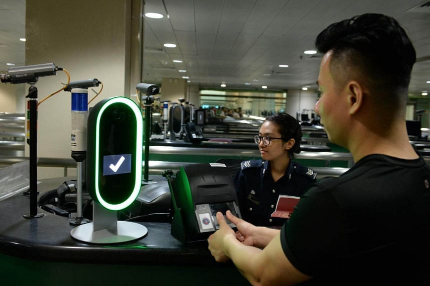 ICA officers demonstrating the use of the Bio-Screen-Multi Modal Biometric Screening System at the Woodlands Checkpoint.