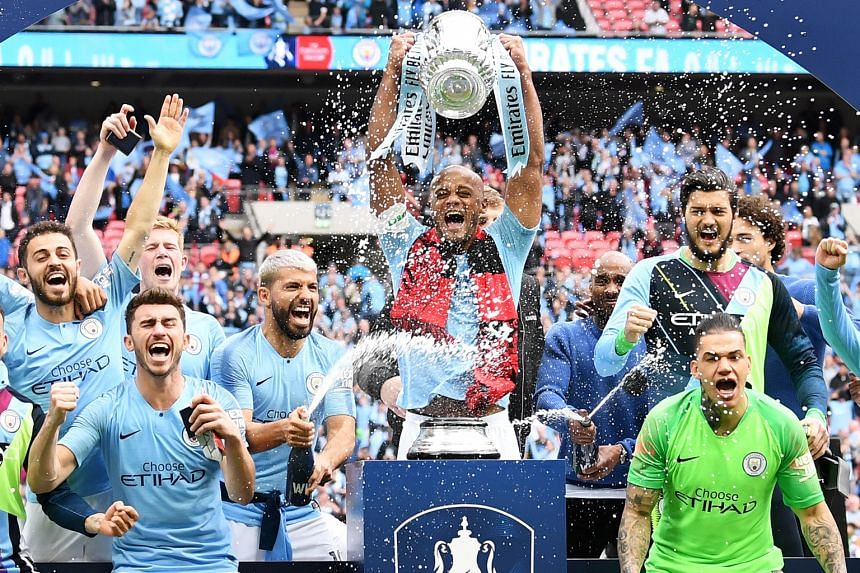 City captain Vincent Kompany lifting the FA Cup after the team thumped Watford 6-0 at Wembley on Saturday, the biggest margin of victory in a final since 1903. Below: City manager Pep Guardiola embracing Raheem Sterling, who scored twice, during the