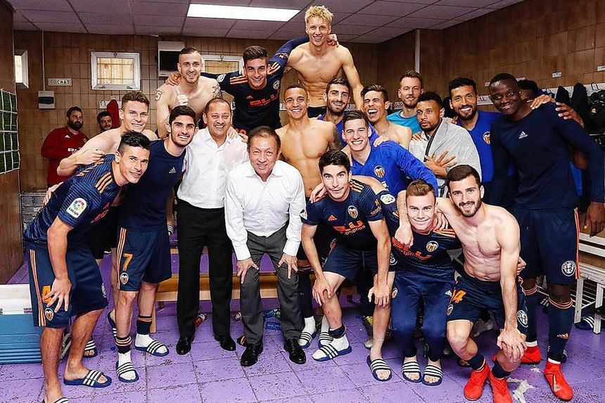 Singapore billionaire Peter Lim with Valencia players after their 2-0 win over Valladolid on Saturday to secure a spot in next season's Champions League - the third time since he bought the club five years ago. PHOTO: INSTAGRAM/VALENCIAFC