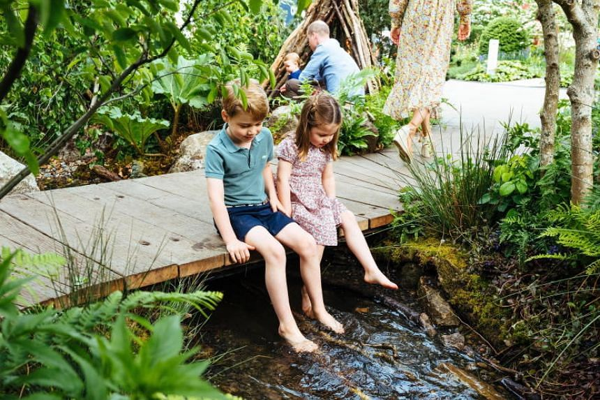 Prince George and Princess Charlotte scrambling barefoot through a stream.