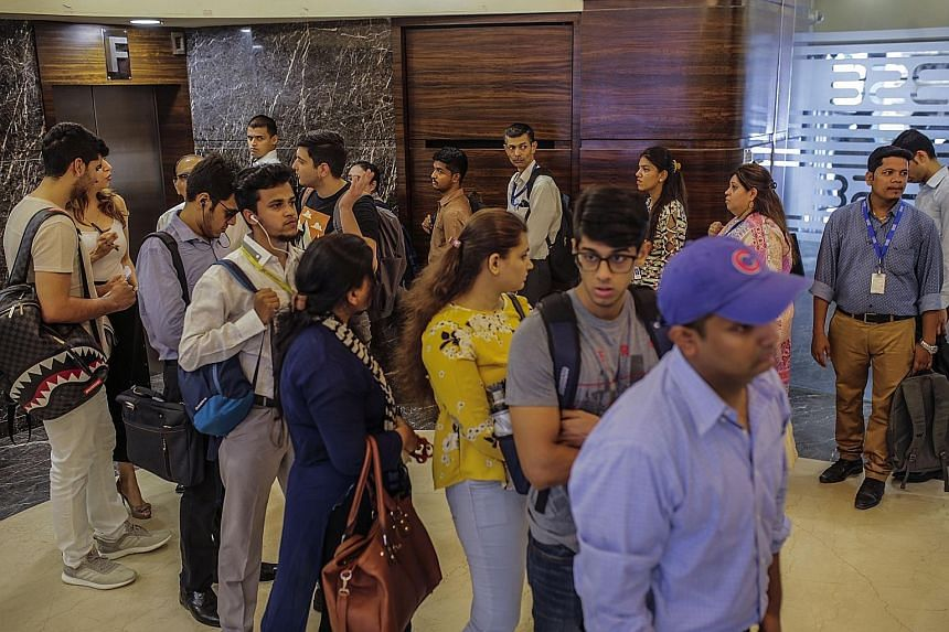 People waiting in line for lifts at the Bombay Stock Exchange building in Mumbai yesterday. Mumbai equities and the rupee soared after exit polls suggested business-friendly Prime Minister Narendra Modi was on course to be re-elected.