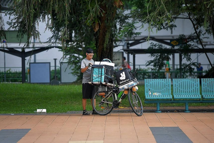 """A Deliveroo delivery rider at Toa Payoh Central. Earlier this year, Deliveroo Singapore switched from a flat $3 delivery fee to a """"variable"""" fee based on factors such as distance and the time it takes the rider to deliver. ST PHOTO: KUA CHEE SIONG"""