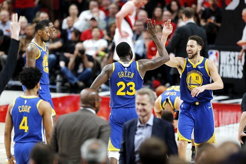 The Golden State Warriors celebrate during overtime against the Portland Trail Blazers in game four of the NBA Western Conference Finals at Moda Center on May 20, 2019.