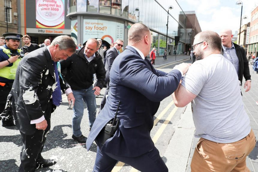 Brexit Party leader Nigel Farage gestures after being hit with a milkshake while arriving for a Brexit Party campaign event in Newcastle, on May 20, 2019.