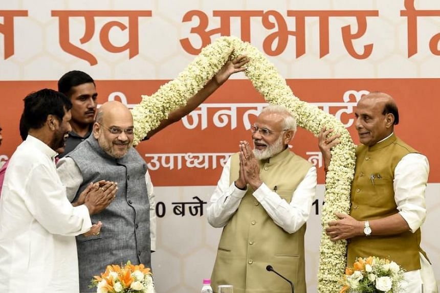 Bharatiya Janata Party president Amit Shah (left) and Indian Prime Minister Narendra Modi are garlanded during a ceremony to thank the Union Council of Ministers for their contribution in India's general election on May 21, 2019.