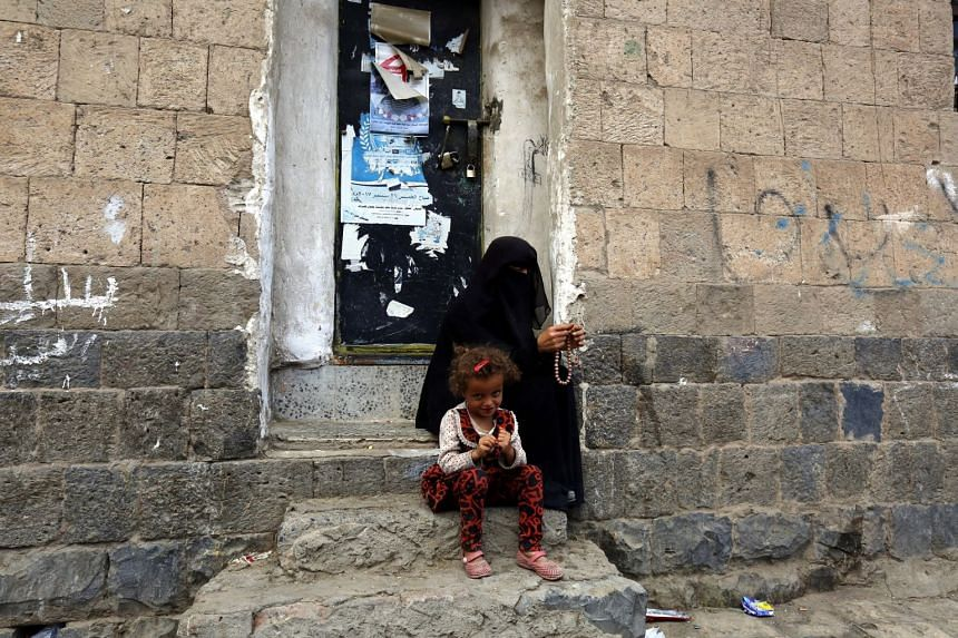 A Yemeni woman and her child wait to receive an aid at a street in the old quarter of Sana'a, Yemen, 13 May 2019.