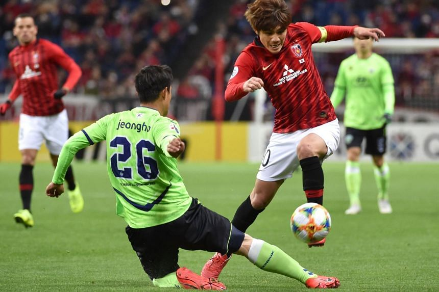 Urawa Reds midfielder Yosuke Kashiwagi (right) and Jeonbuk Hyundai Motors defender Hong Jeongho fight for the ball during the AFC Champions League Group G football in Saitama, on April 9, 2019.