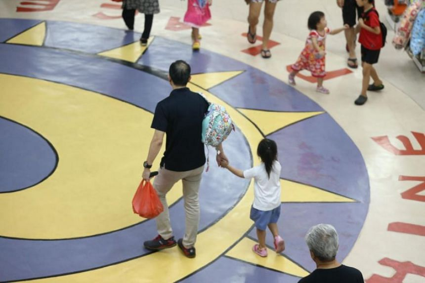 A parent holding his child's hand after fetching her from the childcare centre.